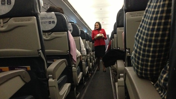 LAN Airlines flight attendant hands out candy during Quito-Cuenca flight.