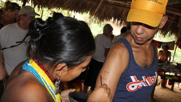 "Angel gets a temporary body paint ""tattoo"" from an Embera woman."