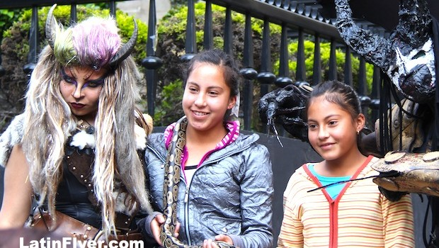 Girls pose with a snake and street performers on Calle Madero in Mexico City.