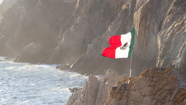 The Mexican flag flies high over the cliff used for diving.
