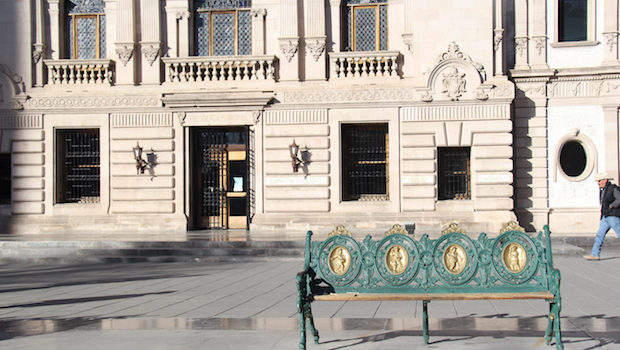 A park bench awaits in front of this building in Chihuahua, Mexico.